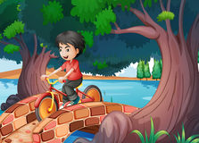 A boy passing the bridge with a bike stock illustration