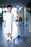 Boy patient holding intravenous iv drip stand in corridor. At hospital Royalty Free Stock Image