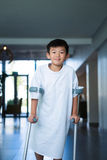 Boy patient walking with crutches in corridor. At hospital Royalty Free Stock Images