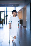 Boy patient walking with crutches in corridor. At hospital Royalty Free Stock Photos