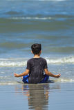 Boy at peace on the beach. Royalty Free Stock Images