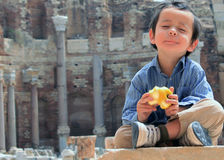 Boy at Peace Eating Apple. Beautiful boy eating an Apple on ruins at Leptis Magna Royalty Free Stock Photography