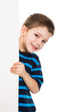 Boy peek out from vertical white banner. Smiling boy peek out from vertical empty banner, isolated on white Stock Photos