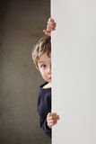 Boy peeking around a wall Royalty Free Stock Image