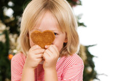 Boy peeking behind gingerbread cookie. A cute boy peeking from behind a love shaped gingerbread cookie in front of a Christmas tree. on white stock photography