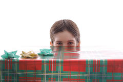 Boy peeking from behind present. Shot of a boy peeking from behind present Royalty Free Stock Photos