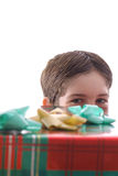 Boy peeking from behind present vertical. Shot of a boy peeking from behind present vertical Stock Photo