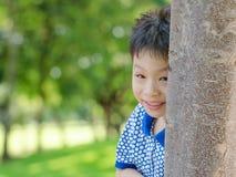 Boy peeking from behind tree Stock Photos