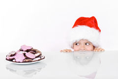 Boy peeking at the christmas gingerbread cookies Royalty Free Stock Images