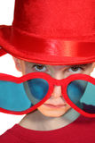 Boy Peeking Condescendingly Over Heart-Shaped Glas. Extreme closeup of a serious boy wearing a red top hat and condescendingly peeking over over-sized heart Royalty Free Stock Images