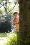 Boy (8-10) peeking out from behind tree, smiling, portrait Royalty Free Stock Image