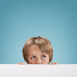 Boy peeking over a white board Stock Photos