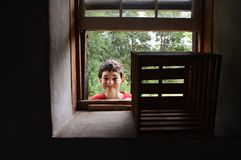 Boy peeking through window Stock Photos