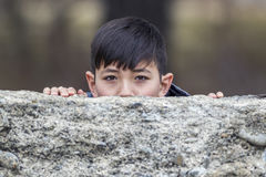 Boy peeks out from behind wall. A playful boy peeks out from behind an old stone wall royalty free stock photo