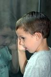 Boy peeks in window. Boy peeks through the window. His image is reflected on the glass royalty free stock photo