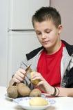 Boy peeling potatoes. A teenage boy helping his mother in the kitchen, peeling potatotes Royalty Free Stock Photo