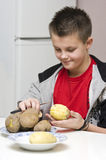 Boy peeling potatoes Royalty Free Stock Images