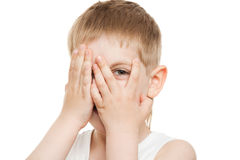 Boy peeping out through fingers. Over white background stock images
