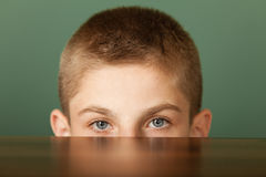 Boy peeping out table surface Royalty Free Stock Photo