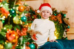 Boy peeps out from behind the Christmas tree royalty free stock photography