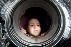 Boy peer into get old washer Royalty Free Stock Photography