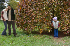 Boy peering at girl hiding in tree Royalty Free Stock Photos