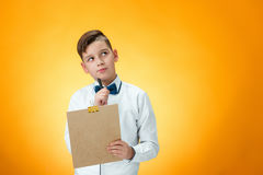 The boy with pen and tablet for notes. On orange background Royalty Free Stock Images