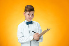 The boy with pen and tablet for notes. On orange background Stock Photos