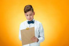 The boy with pen and tablet for notes. On orange background Stock Photo