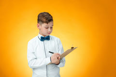 The boy with pen and tablet for notes. On orange background Royalty Free Stock Image