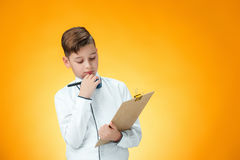 The boy with pen and tablet for notes. On orange background Royalty Free Stock Photography