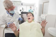 Boy with perfect teeth scared of the dentist. Young teenager is terrifed at the dentist Royalty Free Stock Photo