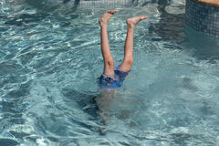Boy performing handstand in swimming pool Royalty Free Stock Image
