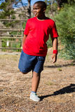 Boy performing stretching exercise during obstacle course training Stock Photography