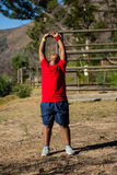 Boy performing stretching exercise during obstacle course training Stock Images