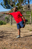 Boy performing stretching exercise during obstacle course training Stock Photo