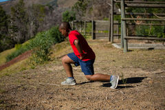 Boy performing stretching exercise during obstacle course training Stock Photos
