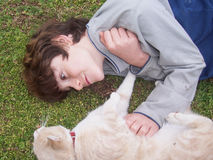 Boy and pet cat at play. 10 year boy playing with pet cat in field Stock Image