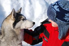 Boy and pet dog. A little boy talking to his pet dog in the snow Stock Photo