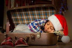 Boy& x27 ; petit somme de Noël de s à l'intérieur de valise photographie stock libre de droits