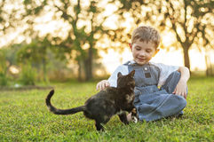 Boy petting cat Stock Images