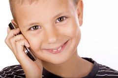 Boy on the phone. Portrait of a school boy using Daddy's mobile phone. Isolated. White background Royalty Free Stock Photography