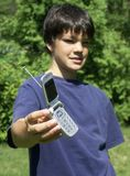 Boy and phone#2. Boy holding out cll phone ,focus on phone royalty free stock image