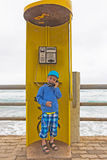 Boy in a phone booth Royalty Free Stock Images