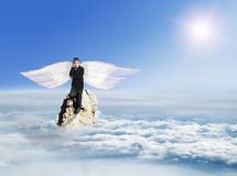 The boy with the phone in the costume with Angel Wings on a rock Royalty Free Stock Photo