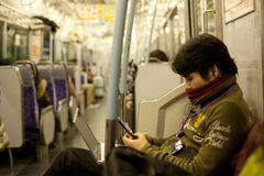 Boy  phone  laptop. Boy Playing mobile phone and laptop in the subway in tokyo japan Stock Image