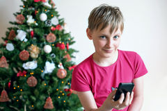 Boy with the phone near a Christmas tree Royalty Free Stock Image