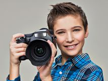 Boy with photo camera taking pictures. Royalty Free Stock Photography