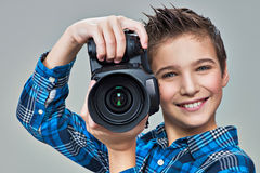 Boy with photo camera taking pictures. Royalty Free Stock Photo