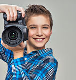 Boy with photo camera taking pictures. Portrait of the caucasian boy with digital camera in hands stock image